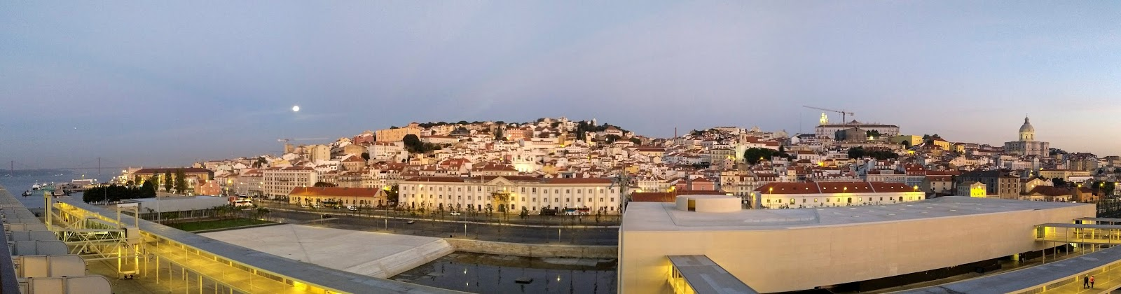 A panoramic capture of Lisbon with the moon setting at dawn.