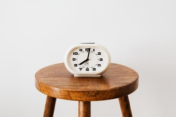 Relógio branco sobre um banco de madeira