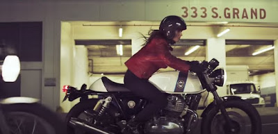 Woman rider on white Royal Enfield motorcycle.