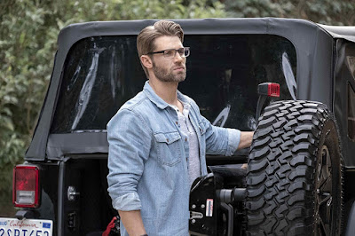 Mike Vogel stands outside his Jeep in dark rimmed glasses staring into the distance in Netflix's new movie Secret Obsession
