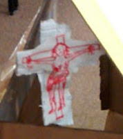 Detail from a created anchorhold - a hanging white cross featuring Christ crucified drawn in red ink