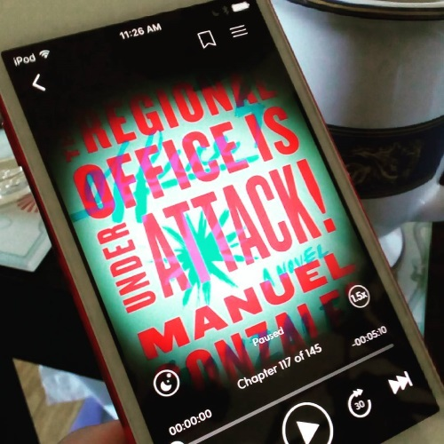 A white iPod with The Regional Office Is Under Attack! on its screen appears very close to the camera, at an angle. A white and blue teacup is visible in the background. The audiobook's cover features the title in red against a pale teal background.