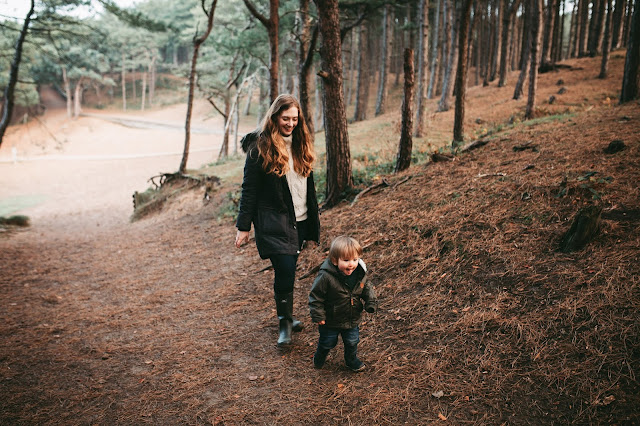 image shows a mother and son walking in the woods