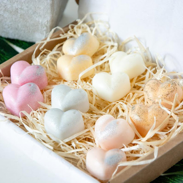 a box filled with natural straw coloured shreds. There are heart shaped wax melts on top in shades of white, pink, and peach, with some silver glitter in them