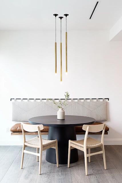 black modern pedestal round dining table with a floating bench on wall with a padded backrest and linear chandelier above
