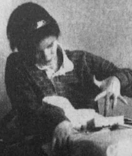 A newspaper photo of a young woman with short, dark hair, using her splayed left hand to operate a communication device.