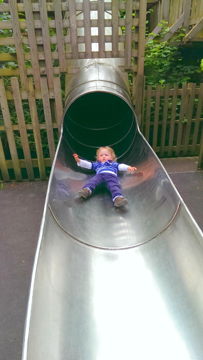 toddler-emerging-from-slide-at--Perrygrove-Railway-adventure-playground