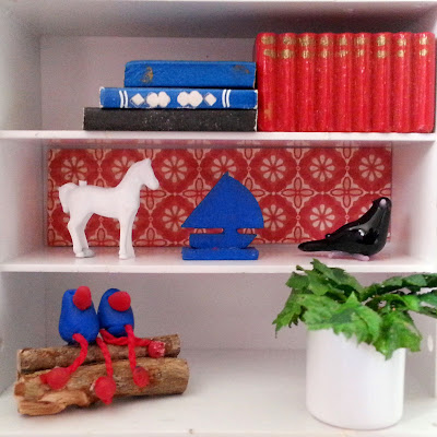 One-twelfth scale miniature retro display shelving containing books, a pot plant, glass bird and various other objects.