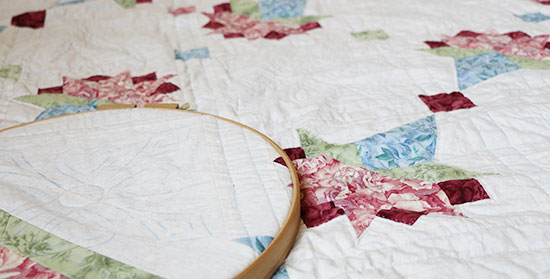Detail of a portion of a Queen size quilt held in a hand quilting hoop with more of the quilt in the background.