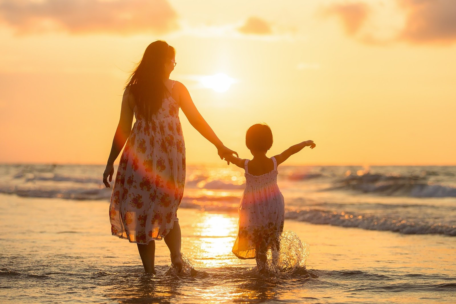 a mom and child facing away from the camera walk through the ocean surf during sunset to illustrate a blog post about war movies that are family-friendly