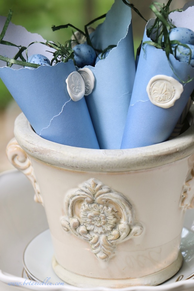 French Country Sunspace urn holds blue DIY Easter paper cones with white fleur de lis wax seals
