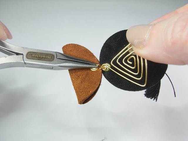 Hooking the wire spiral triangle onto the two leather circle pieces