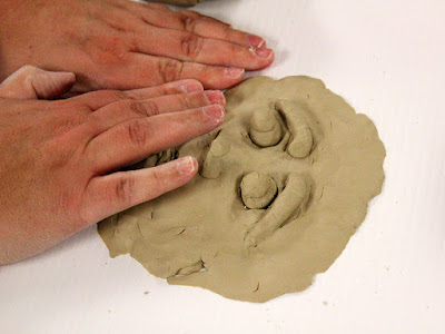 Artists hands over clay working on self portraits