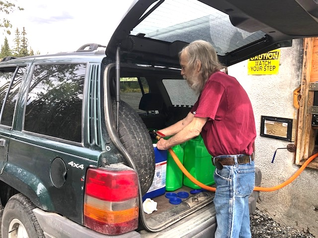 Plastic water jugs filled with water in the back of an Alaskan vehicle, 2020
