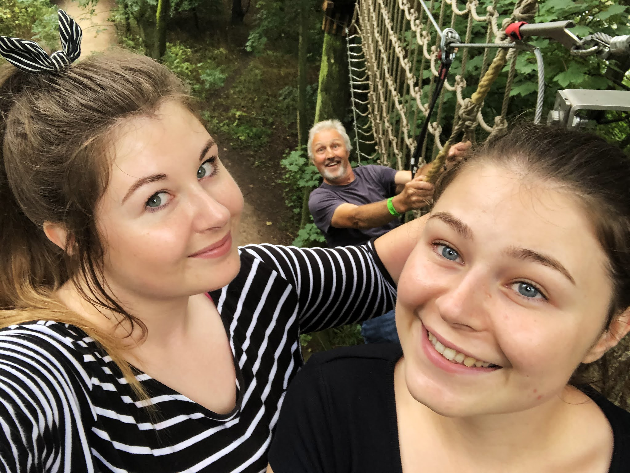 Grace and her sister posing for a photograph up in the trees. Her dad can be seen in the background hanging on to one of the crossings.