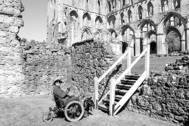 Me in my mountain trike at the bottom of a flight of wooden steps. There is no way I could possibly climb them but I'm pointing up with a cheeky grin, as though I might give it a try.