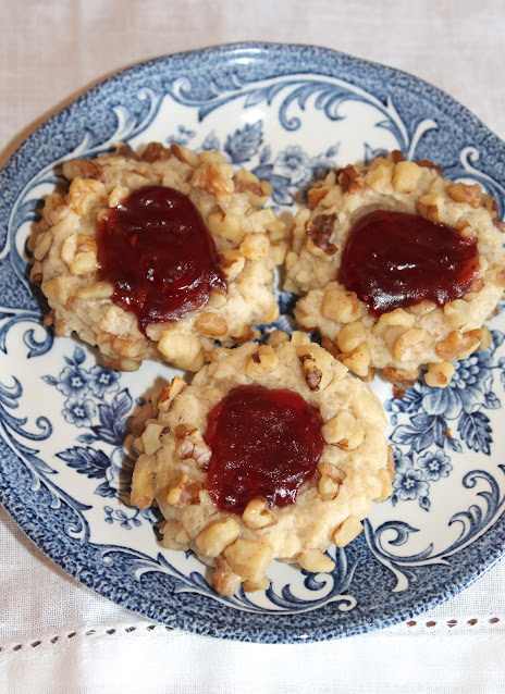 Close-up of finished thumbprint cookies filled with raspberry jam.