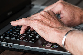 hands-old-typing-laptop-internet