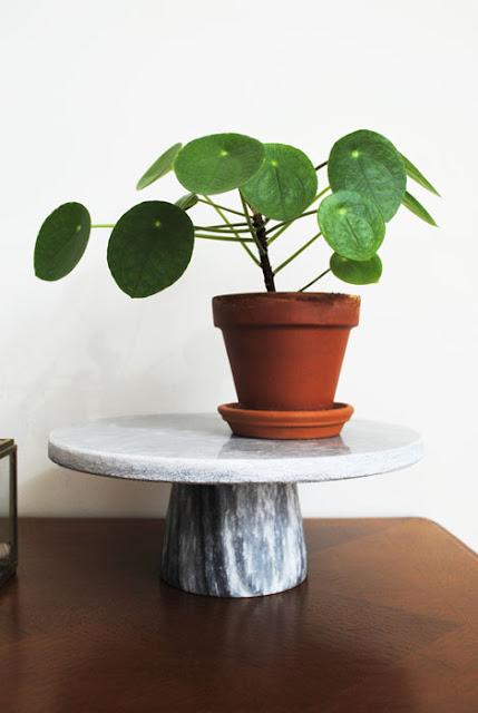 Taartstandaard van marmer met daarop een aardewerken potje met een pannekoekenplantje oftewel Philea Peperomioides