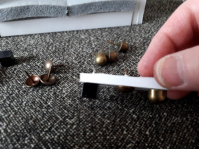 Had holding a small piece of foam core board with various-shaped tacks stuck into the bottom of it. Behind are more of the tacks on a piece of fabric, and a half-made one twelfth scale miniature sofa.