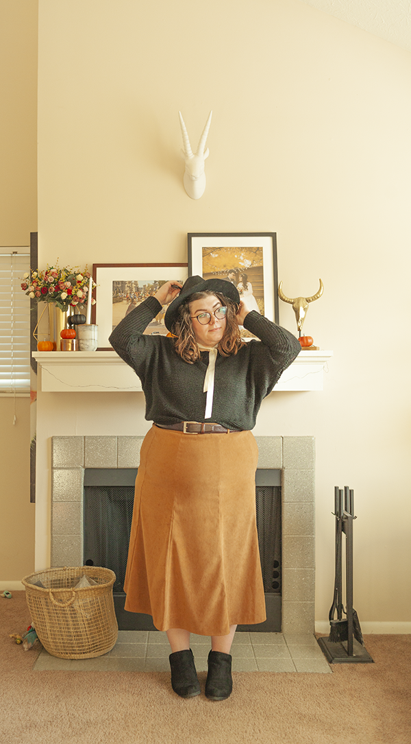 An outfit consisting of a black wide brim hat, black dolman sweater tucked into a brown A-line tea length skirt with black ankle boots and a white silk ribbon tied loosely around then neck.