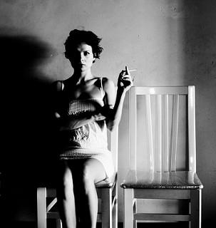 Fujer sentada fumando. A su lado silla vacía