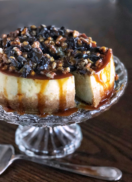 cheesecake covered in pecans, chocolate and caramel sauce