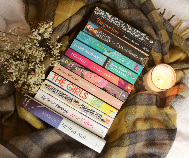 Stack of books with spines facing upwards next to a candle and flowers