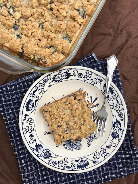 A plate with a sour cream and raisin oatmeal square next to the pan.