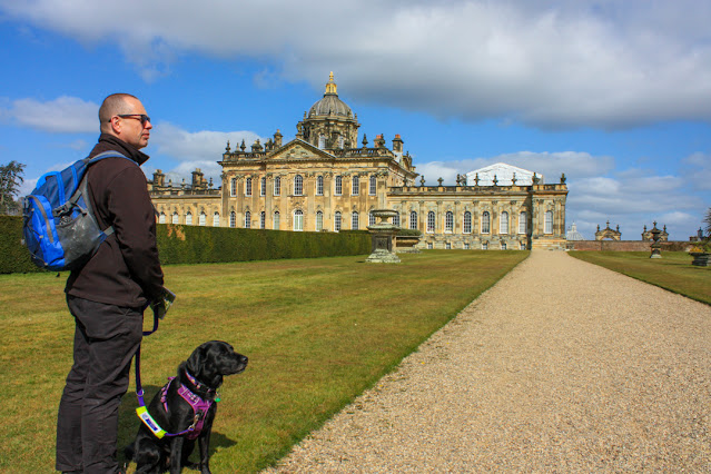 Castle Howard in the distance, Neil and Liggy (black lab) are standing at the side of a gravel path with an expanse of lawn behind them.