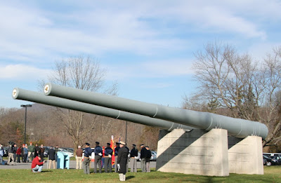 People in military uniform and civilians gather near two 44-foot gray artillery guns mounted on a concrete pedestal to mark the anniversary of Pearl Harbor.