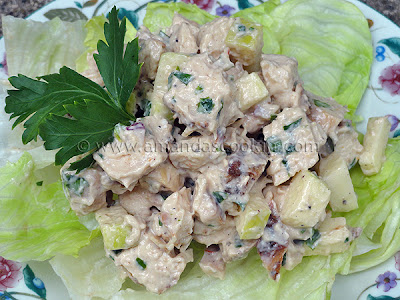 A close up photo of chicken salad on a piece of lettuce.