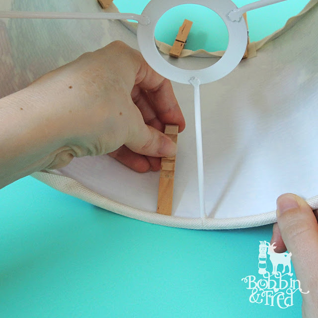 using a peg to tuck the fabric under a lampshade ring by Bobbin and Fred