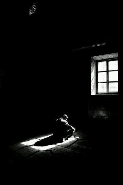 Imagen de un hombre solo, sentado en la oscuridad a la luz de una ventana.