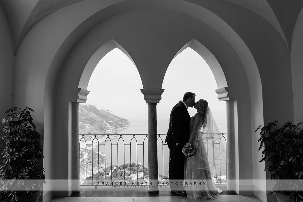 Bride and groom kiss in arched window
