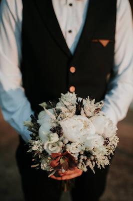 Novio llevando en las manos un ramo de novia