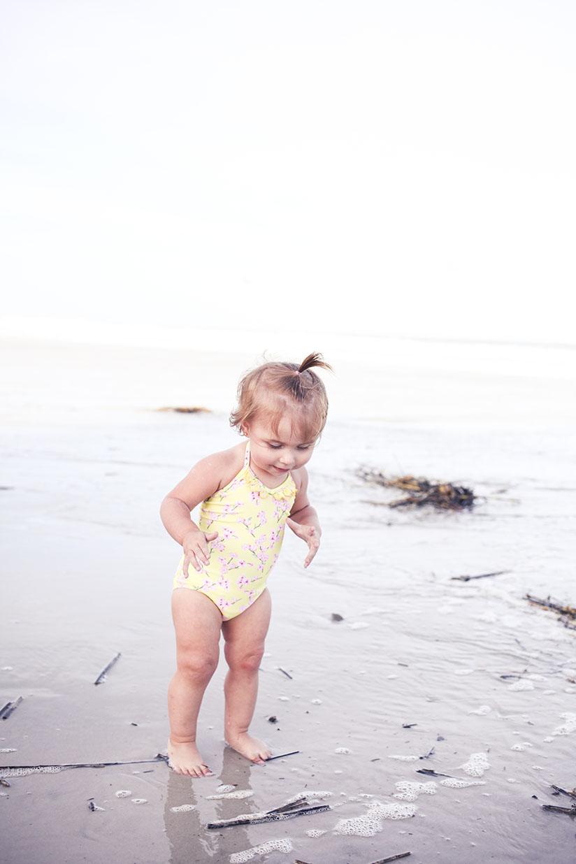 toddler playing on the beach wearing swimwear by Sunuva