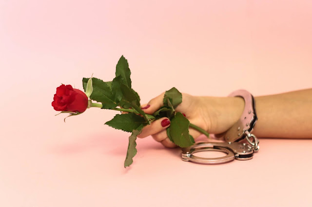 Women in handcuffs holding red rose: Photo by Dainis Graveris on Unsplash