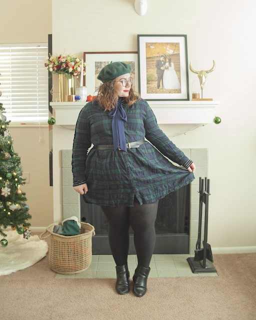 An outfit consisting of a forest green beret, a black and white turtleneck under a green plaid dress and black ankle Chelsea boots.