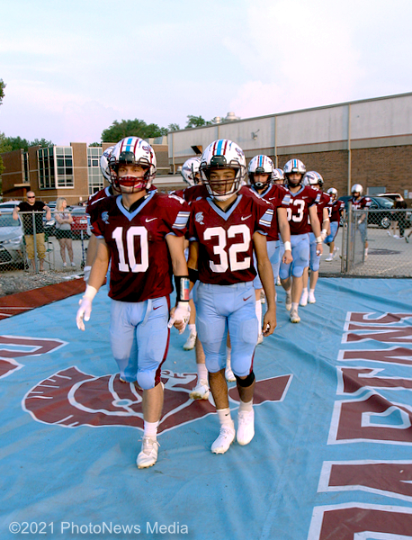 Coby Miller (left) and Isaiah Moore lead the St. Joseph-Ogden football team to the field