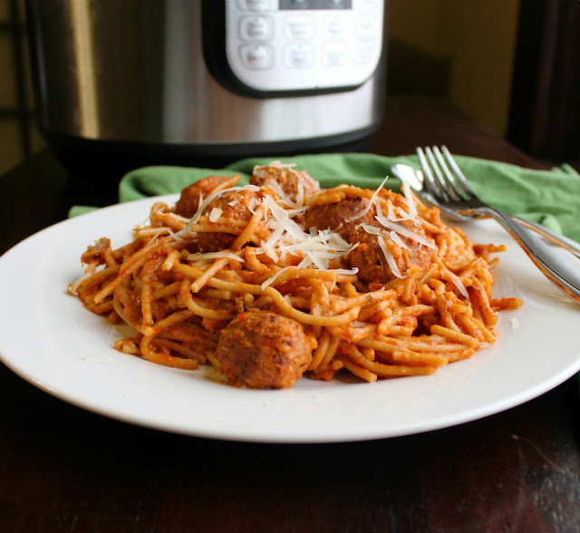 pile of spaghetti and meatballs on plate in front of instant pot