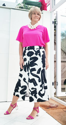 Is This Mutton style blogger Gail Hanlon in fuchsia top, layered chunky pearl necklace, black and white abstract print skirt and pink sandals
