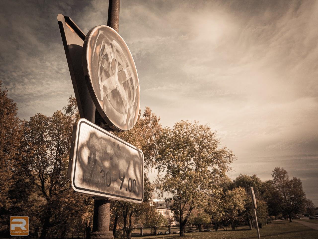 Ar krāsu aizkrāsota ceļa zīme uz debesu fona