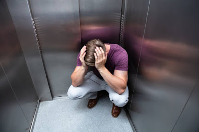 homem em pânico dentro de elevador parado