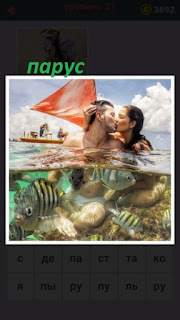 мужчина и женщина в воде целуются на фоне паруса от яхты