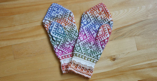 Hand knit colorwork wool mittens overlapping each other on a light wood background.
