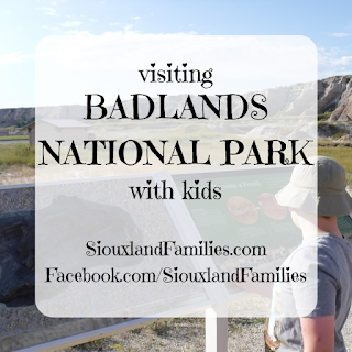 "In background, a boy in a gray shirt and khaki bucket hat looks at an information panel at Badlands National Park, with rock formations visible in the distance. in front, the words "" Visiting Badlands National Park with Kids"" and ""SiouxlandFamilies.com  Facebook.com/SiouxlandFamilies"""