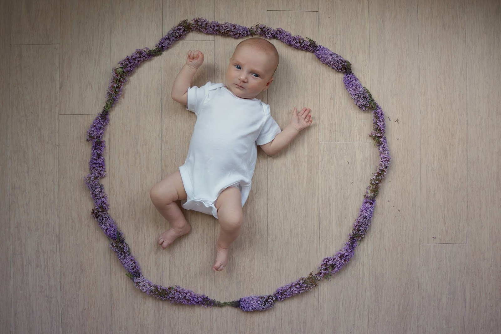 baby in a circle of flowers