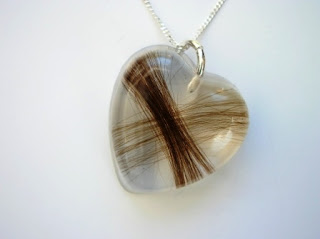 Heart shaped pendant containing two locks of hair