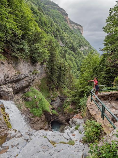 Niña asomada a un mirador con un paisaje de montaña